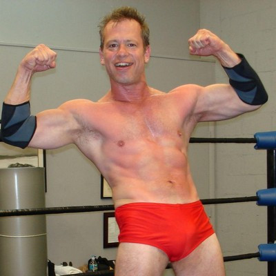 muscle jock wrestler posing in pro wrestling ring at pro show