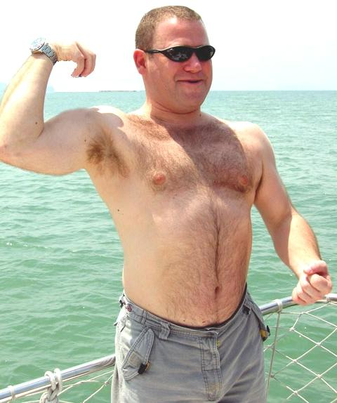 very hairy daddy bear flexing big muscles on boat